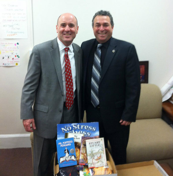 Rep Gordon with Rep. Paul Brodeur (D-Melrose) pays off his bet after Melrose High School's football team defeated Burlington in the quarterfinal round, with a box of books destined to the Melrose Food Pantry.  Courtesy photo